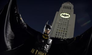 A man poses in front of the bat signal projected on to City Hall in Los Angeles for Adam West.