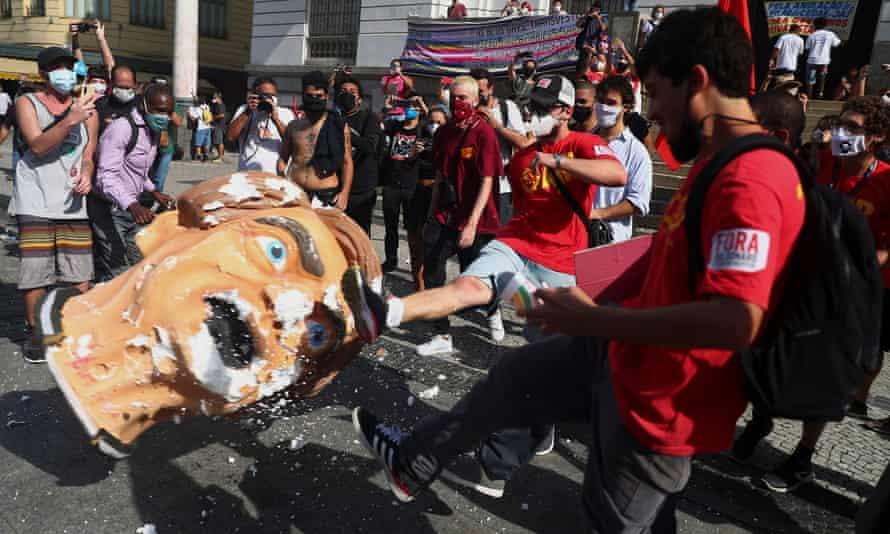 Manifestantes chutam um adereço de cabeça representando o presidente do Brasil, Jair Bolsonaro, durante um protesto no Rio de Janeiro no sábado.
