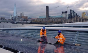 Solar panels are installed on Blackfriars station with the old Bankside coal-power station (now the Tate Modern) in the background. Coal use fell by 22% while solar energy rose by 50% in 2015, figures show.