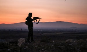A Syrian rebel fighter aiming his Kalashnikov assault rifle near the frontline of the fight against government forces in Deraa in July 2018.