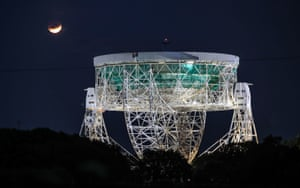 A partial lunar eclipse is visible above the Jodrell Bank Observatory in Cheshire, England