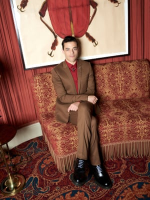 Rami Malek in a brown suit, red shirt and black shoes, sitting cross-legged on red patterned upholstery