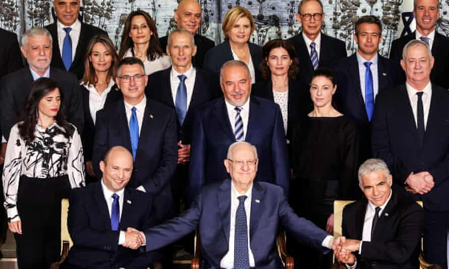 Israel's president, Reuven Rivlin, sits next to Prime Minister Naftali Bennett and the foreign minister, Yair Lapid, as they pose for a group photo with ministers of the new Israeli government