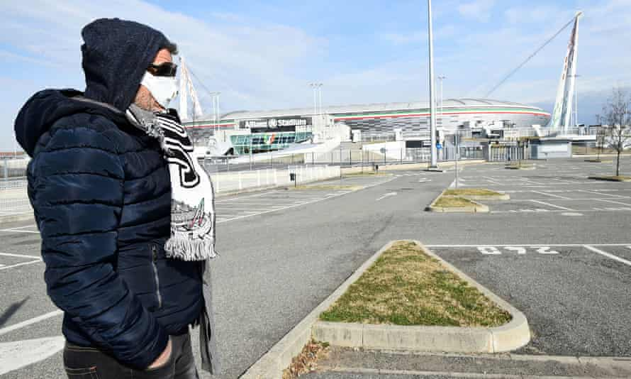 A fan with a face mask walks past the Allianz Stadium in Turin.