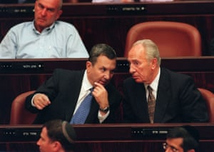 Peres conferring in parliament with a man in suit and tie