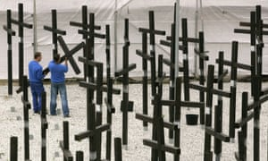 Workers take down the crosses of the Mauermuseum's memorial to those who died because of the wall.