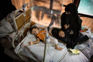 Samira Abdullah watches her daughter Qasima, who is on an IV drip, at a screening tent outside the cholera ward of the al-Sabeen women and children's hospital.