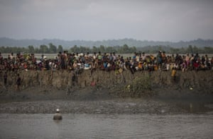 Rohingya Muslim refugees gather on a mud bank after security forces temporarily stopped people crossing into in Whaikhyang, Bangladesh.