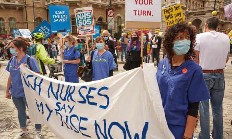 Nurses in blue uniforms carrying a variety of protest banners during a march