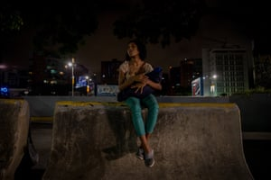Liliana holds her 29-day-old son Angel in her arms on a street at the 'Las Mercedes' district in Caracas