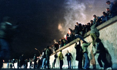East German citizens climb the Berlin Wall after the opening of the border was announced