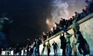 East Germans climb the Berlin Wall at the Brandenburg gate on 10 November 1989.