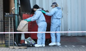 Scene of crime officers search through a bin in Seven Kings, Ilford, near to where three people died after being stabbed.
