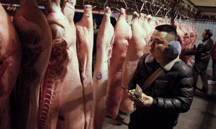 Chinese pork vendors select the product in a pork wholesales hall of a market in Beijing, China.