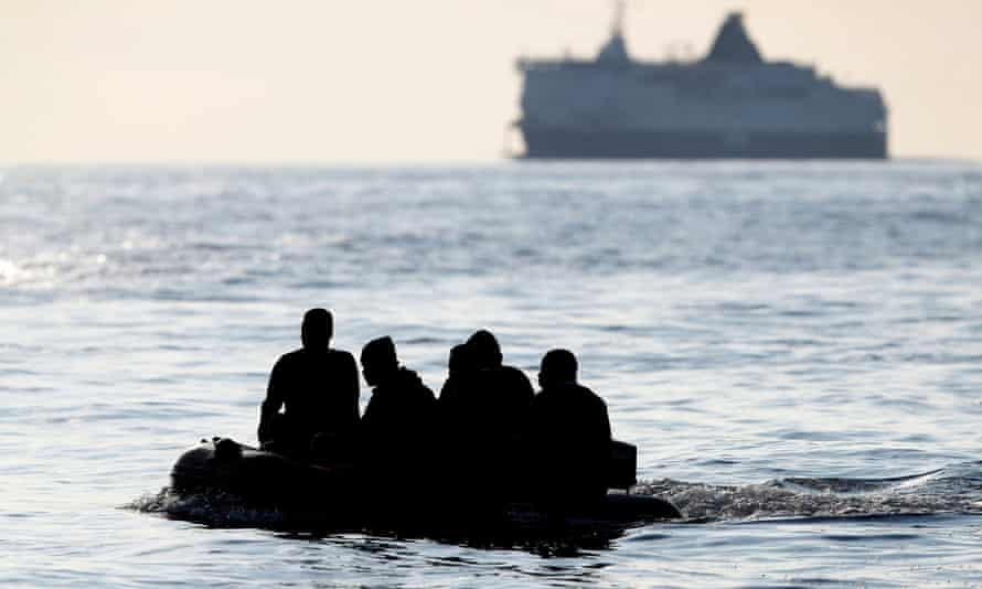 People claiming to be from Darfur, Sudan, cross the Channel in an inflatable boat near Dover on Wednesday