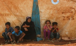 Displaced Syrians rest by a tent