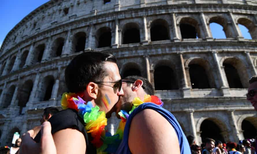 A couple kiss in front of the Coliseum