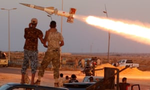 Fighters of Libyan forces allied with the UN-backed government fire a rocket at Islamic State fighters in Sirte.