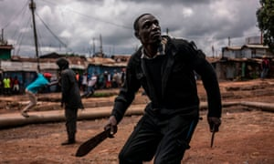 A protester brandishing a machete and a knife prepares to take cover from incoming tear gas canisters during clashes with police forces in Kibera, Nairobi, on October 26, 2017.
