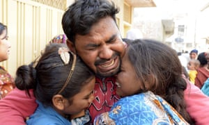A man and children in Lahore at the funeral of a family member killed in the blast.