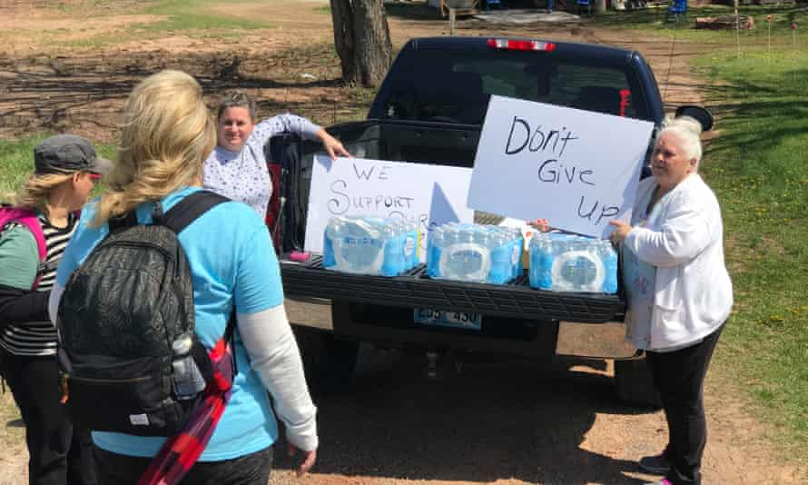 Beverly Langley, right, hands out water and encouragement as Oklahoma teachers march to Oklahoma City.