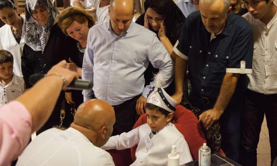 Adults eagerly watch as a scared-looking boy  is circumcised in Turkey.