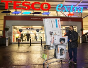 A man leaves Tesco with a TV bought during the Black Friday sale