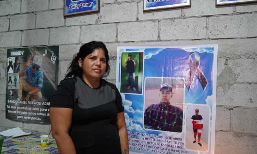 Maria Elena Villacís standing in front of a poster showing her deceased brothers at her home on the outskirts of Guayaquil, Ecuador