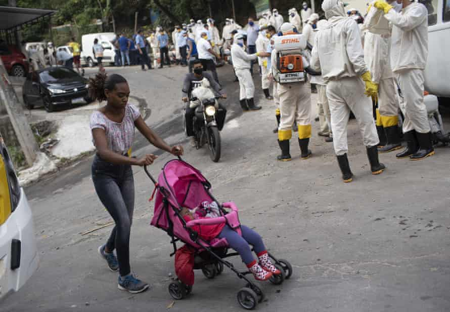 A woman walks past water utility workers will disinfect the Turano favela in an effort to curb the spread of the coronavirus in Rio.