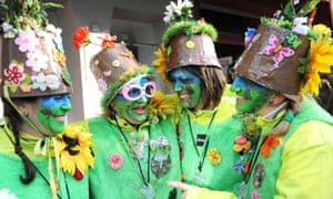 A group of four paraders, dressed in green and lemon outfits with plant pots on their heads at the Dunkirk carnival, France.
