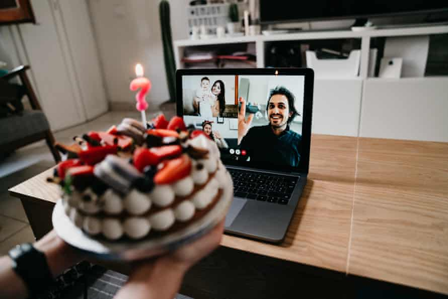 Young woman celebrates her birthday with friends and relatives during quarantine.  She is making a video call with a laptop