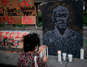 A woman lights a candle during a protest in front of the US embassy in Mexico City