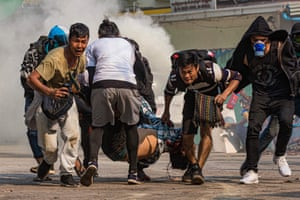Protesters carry a wounded man shot by the security forces in Yangon