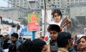 A little girl rides on her father's shoulders at a book fair in Kolkata.
