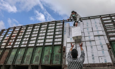 Workers for the United Nations Relief and Works Agency (UNRWA) unload food supplies for refugee families in Gaza City.