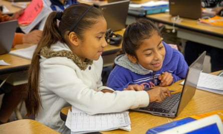 Hispanic third grade students enter information in their Google Chromebook laptop computers in a San Clemente elementary school classroom.