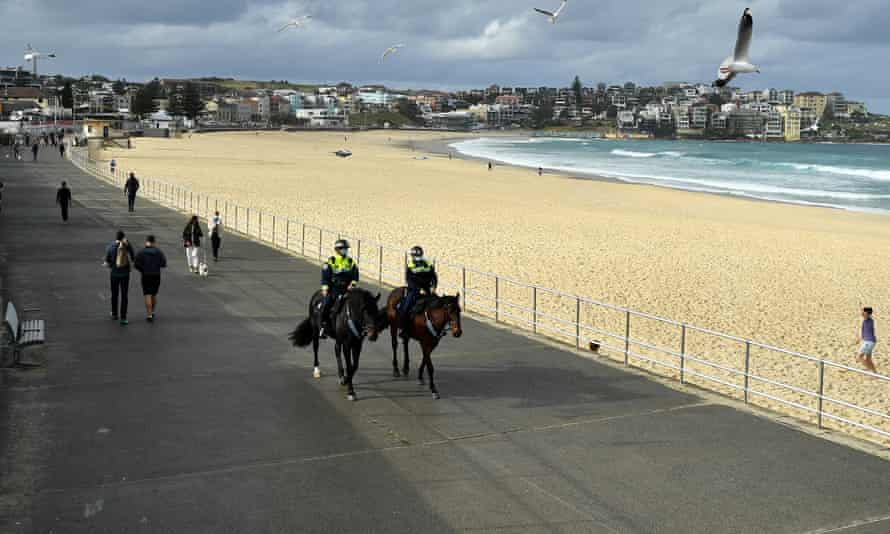 Mounted police patrol Bondi Beach in Sydney, Australia on 28 June. With the entire state of NSW under Covid lockdown restrictions, check our full guide to the new and updated coronavirus rules around wearing face masks, home visitors, the 5km radius travel limit, curfew and exercise time limits.