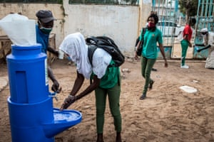A High School student at the Lycee Blaise Diagne washes her hands as she arrives for her first day back at school in Dakar on 25 June, 2020.