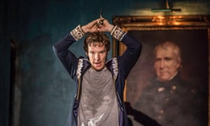 Benedict Cumberbatch plays Hamlet at the Barbican, holding a dagger over his head