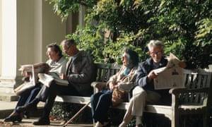 Four elderly people sitting on a park bench