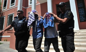 Turkish officers escorted by Greek police officers leave court in Alexandroupoli