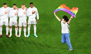 A protester holds a rainbow flag as the Hungary team sing their national anthem