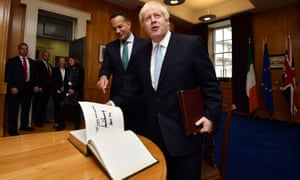 Boris Johnson (right) opening the guestbook at the page signed by Donald Trump and his wife Melania before holding talks with Leo Varadkar (centre) at Government buildings in Dublin