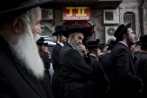 Ultra-Orthodox Jewish men gather around the body of Yeshayahu Kirshavski during his funeral in Jerusalem.