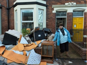 A resident of Warwick Road stands by her belongings that have been ruined by the floods, 11 December 2015