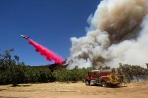 An air tanker drops fire retardant to a brush fire