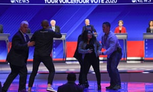 Protesters are escorted off the stage during the debate.