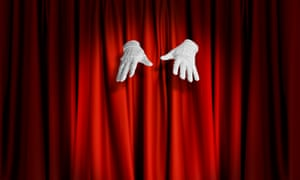 Magician's white gloved hands floating in front of red stage curtains