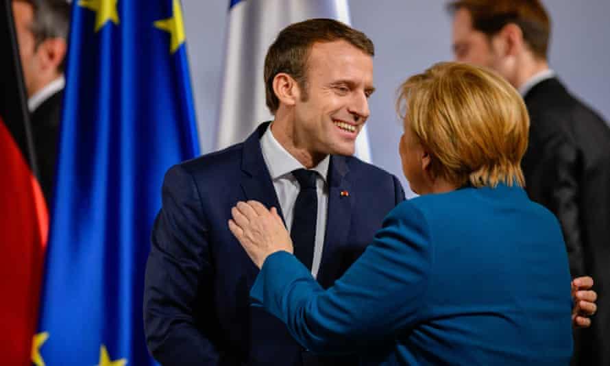 Angela Merkel (R) and Emmanuel Macron greet each other in Aachen.