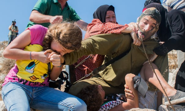 Palestinian girl biting an Israeli soldier trying to release her brother from the hand of the soldier in the West Bank village of Nabi Saleh.